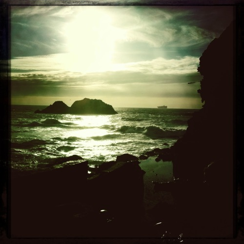 "Ship on the Horizon. Pacific Ocean. Sutro Baths. John S Lens, Cano Cafenol Film, No Flash, Taken with Hipstamatic Otis' ""Sitting on the Dock of the Bay"" was conceived when he was living in Sausalito, not long after his famous Monterey Pop performance. He didn't live to see the song come out; his plane crashed into Lake Monona in Madison, WI. I thought often of him when I was in school there, and these days I think about the song whenever I see a ship roll in, or roll out. I've seen it a few times but it's still magical to watch one steam into the sunset."