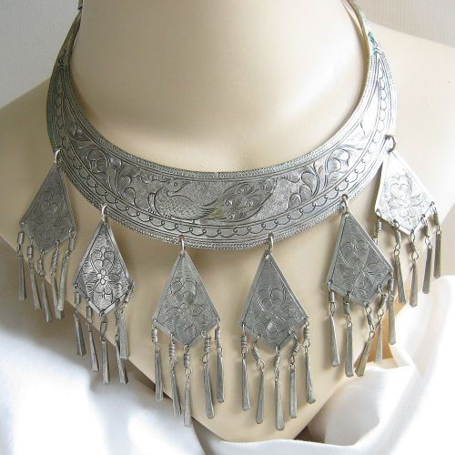"This is a beyond gorgeous Vintage Antique Silver Tibetan Collar Necklace!   This necklace dates from the 1920's to 1930's, and is fabulously engraved with a Peacock, flowers and leaves, along with decorated borders.  The top ends next to the clasp appear to be engraved with fish heads.  There are 6 triangular dangles with exotic floral engraving, and 3 dimensional tubular dangles that hang from them.   The width at the center of the collar portion measures 1 ¼"" – triangular dangle pieces each measure 1 5/8"" long by slightly more than 1 ½"" – and the tubular dangles measure about 1 ¼"" in length.  The total measurement at the center is an awesome 4 ¼"" long!   This piece has tested at 900 Silver, commonly known as nickel silver, German silver, or coin silver.  This piece has its natural patina, but you could polish the necklace to a bright shine if desired.  This wonderful piece will fit any regular size neck.   One of the most fabulous pieces I've ever offered!! Check it out at:  www.myvintagejewels.etsy.com"