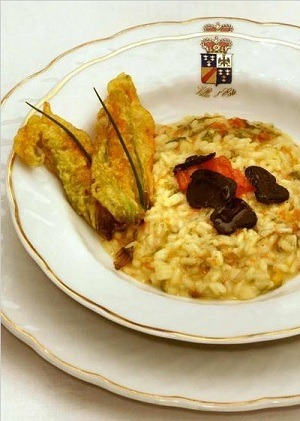 An exclusive recipe from Tales of Risotto and the master chef at Villa d'Este, available from Glitterati Incorporated. Risotto con seppioline farcite e  basilico /   Risotto with  Small Stuffed  Cuttlefish and Basil Ingredients 6 servings 24 small cuttlefish cleaned  ( 6  cut in   small stripes) 2 sliced of white bread cut in cubes 2 tomatoes without skin and  seeds cut in small cubes 2 oz  greens ( spinach  ? ) washed and  thinly cut 1  whole egg 2 tablespoons cream 2 tablespoons  pecorino cheese , grated ½  garlic clove, minced 2 tablesppons of extra virgin olive oil 1 onion thinly sliced 1 glass  vegetable  broth 2 glass  dry white wine fresh basil leaves In a stock-pot  mix bread with the cream  : let it rest until it becomes soft, mixing with a fork.  Then add the greens, the egg, the pecorino cheese, the garlic and half of the tomatoes, salt,pepper and 1 tablespoon of olive oil.  Mix well  and use  to stuff the cuttlefishes . then close  them with a  tooth pick. Sautè onion in oil, add the cuttlefishes and  the remaining tomatoes. Cook for a few minutes. Pour  over white wine, let evaporate then add the vegetable broth. Cover and let it cook on low flame for about 20/30 minutes. In the meantime prepare a basic risotto with the following ingredients : 2 cups  Carnaroli rice 6 cups vegetable broth 5 tablespoons of butter  1 tablespoon  extra virgin olive oil 1 small onion, finely chopped salt and pepper 3 tablespoons Parmesan cheese, grated 1 cup dry white wine , or Spumante ( pour over rice. Let evaporate  then start adding broth ) 1 tablespoon   fresh basil, minced When half done add the cuttlefishes cut. When done,  remove the pan from the heat and stir in the remaining butter, the Parmesan cheese and the minced basil. Serve on hot dishes with the  cuttlefishes  and garnish with fresh basil leaves