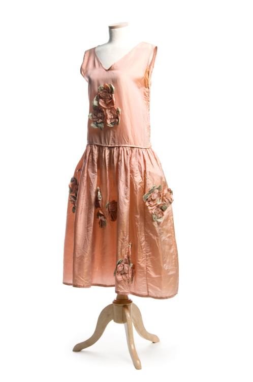 Pink silk robe de style dress, 1920s. This lovely dress is ornamented with pink and green silk rosettes. The full, gathered skirt has sewn in hip panniers, an innovation introduced by designer Jeanne Lanvin in 1915 to feminize the straight silhouette popular at this time and the later boyish, flapper style of the 1920s. While this dress does not bear a label, it was most certainly influenced by Lanvin's ideas.  It was worn by Mary Sinkler deSaussure McQueen (1899-1977) in Charleston. These thigh hoops or panniers hearken back to the extremely wide side bustles or panniers of the 18th century. In those, hips were sometimes so wide it was difficult to walk through a door. The 1920s panniers are much subtler, offering a gentle fullness to the bouffant skirt. Lanvin's favorites included solid colors of silk taffeta ornamented with silk flowers and ribbon bows, similar to the ones on this dress. This dress is currently on exhibit in Charleston Couture. Come visit it for yourself! TEXTILE TUESDAYS: Each Tuesday we post a piece from our textile collection.  Some items have been on exhibit, some will eventually be shown in our new Historic Textiles Gallery and some may be just too fragile to display. We hope you enjoy our selection each week – do let us know if there's something in particular you'd like to see on TEXTILE TUESDAY! #TextileTuesday