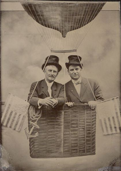 ca. 1870-1910, [tintype portrait of two gentlemen in a mock balloon draped with flags] via Christopher Wahren Fine Photographs