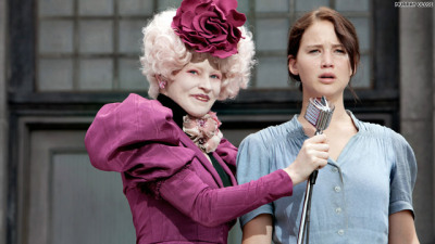 "Effie Trinket, Capitol fashionista, introduces the befuddled Appalachian heroine of the Hunger Games, Katniss Everdeen.  - So: I have a lot of thoughts about The Hunger Games and fashion.  There is a lot of fashion in the series, especially in the first two books, but I never really thought about it until going to see the movie this weekend.  The increased importance of fashion in a visual medium, I guess.  - Down With The Capitol and all that, but honestly, the Capitol fashions are really good.  They're so sick.  I can't get over how good they are.  Effie Trinket may be birdbrained and unsympathetic as hell, but she knows shoulderpads.  Politics aside, I can't believe that most fashion editorials inspired by the series are about Katniss's damn side braid.  (One exception: the Capitol Couture tumblr.) - Which leads me to: it's a little annoying to me that the most vapid characters from the Capitol have the most effeminate and stylised fashion.  it's kinda crypto-homophobic, all this avant-garde gender-bending fashion presented as the height of decadence.  - I mean, yes, totally, the underclass in a dystopian society who spend all their time thinking about their next meal are going to have less time to spend on their fash than the extravagant fashionistas of the Capitol.  But it's usually the case in our own society that it's underclass fashion that's stereotyped as gaudy and monstrous, and the upper classes who have the resources to do classic and subtle styles.  Classic is expensive, and it's inherently expensive: good classic style is defined not by creativity or colour or anything else that's accessible to people with no money, but by quality of materials and tailoring. - And indeed, the more eeeeeeeevil and serious of the characters from the Capitol (President Snow and his ilk) have more sober and gender-conforming fashions, basically suit-and-tie stuff.  But also see for example how Cinna — a sympathetic fashion designer who is continually presented as truly cutting-edge, the last person you'd expect to have a conservative dress sense — is coded as sympathetic the minute we are introduced to him by Katniss noticing and approving of his comparatively subdued personal style.  He does have signature gold eyeliner, so it's all relative I guess. - On the other hand, it appears that Panem doesn't have the kind of mass production of cheap fashion that we do, or at least it doesn't reach District 12.  They're clearly not working within an economy of fashion that's at all comparable to our own.  Also there's a subtle French Revolution thing going on with the exaggerated hourglass figures and the white curly wigs, which I like.  - All that aside, I think we can all agree that Cinna is the best. He's all like, ""don't mind me, I'm just some amazingly creative and talented fashion designer with really good politics and a kind nature who's going to devote my considerable skills to keeping terrified underclass kids alive by making sure they look so damn cute people can't bear for them to die"".  It's one of the only truly interesting depictions of fashion and fashion design I've seen in recent Western pop culture.  - While we're talking visual culture, let's talk about the whitewashing controversy: Jennifer Lawrence is great as Katniss.  But her best efforts aside, the movie is hurt by Katniss being played by an unambiguously white and also very fair-skinned (freckled, even) actress.  The dynamic where she has less privilege than her mother, Peeta, and the village elite (all fair-complected) is continually reinforced in the books by reference to her darker complexion, like her father, like most coal-miners in her district, and like Gale.  It's a super-important sign of her underclass roots.  Likewise, the support and solidarity offered to her with little prompting by Cinna, Rue, Thresh (all characters of colour, although I believe Cinna's race is ambiguous in the books), and District 11 (a predominantly Black community) feels more arbitrary if she's unambiguously white. (This more in-depth commentary at Feminist Film is good.)"