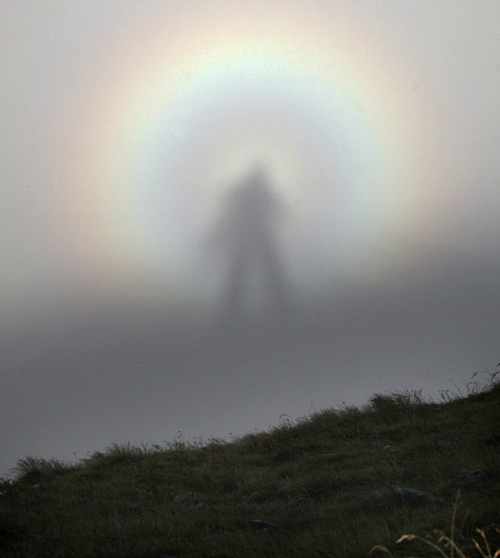 "science:  The Brocken Spectre, here seen in Poland, is an optical phenomenon in which the observer's shadow appears to be magnified on clouds or fog below. The Spectre can be observed from mountaintops when the sun is low and behind you, and there's dense fog or clouds below. It is often accompanied by a glory, a rainbow-like halo that can also be observed when one is between the sun and a layer of clouds, and the movement of the clouds plus the apparent magnification can give the impression of a supernaturally tall ghost being walking the mountain. The phenomenon is named for Brocken, also known as Blocksberg, a mountain peak in northern Germany long associated with witches and devils in local lore and literature. Another place to see it is the Scottish mountain Ben MacDhui, a frequently fog-shrouded peak where legend has it an unusually tall ""Grey Man"" resides. It isn't hard to image how a lone mountaineer—halfway lost and hearing his own footsteps oddly distorted in the mist—could conjure up mythical beings when faced with a ghostly giant in the distance."