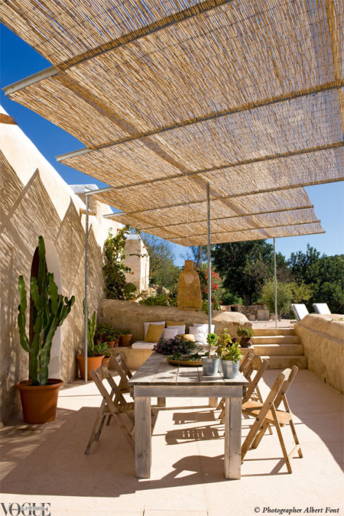 The Ibiza holiday home of rug and textile designer Nani Marquina and photographer Albert Font features a dining terrace with restored wooden table and old cinema chairs from local island shop Sluiz. From 'Unearthed in Ibiza', a story within Vogue Living Mar/April 2012.  Photograph by Albert Font.