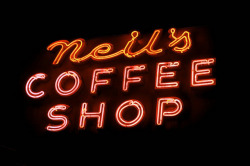 "projectneon:  Neil's Coffee Shop(On Lexington Avenue at 70th Street in the Upper East Side) [Pardon if my sentances don't parse properly — I'm listening to the Beastie Boys as I write this in a futile attempt to drown out the racket of my upstairs neighbors. Oy.] I'm pretty much bound to feel affectionately toward anything with ""coffee shop"" in the title and Neil's has a great sign. Lovely script and block letters in channels hanging over the corner of Lexington Avenue and East 70th Street in glowy pink and deep orange will lead you to an old-school diner in the shadow of Hunter College. The service is not what you'd call attentive, the interior decor is a symphony of beige, and the standard diner fare is nothing to write home about (I had a decent grilled cheese and a disappointing milk shake), but it's an old reliable in a neighborhood with too many snobs and show-offs. Add in a lovely neon sign, and I'm happy. If you're in the neighborhood you should ch-ch-check it out. ……………………………………………. Wanna see some neon from 1970s New York? OK, here you go. (Thanks, Paul.) Wanna see Times Square neon in 1957? Have a look at this. (Thanks, Curt.) Wanna see some fun neon in Austin? Lookee here. EDIT:  Oh, hey, guys — I think I forgot to tell you I wrote a guest post for I Love Old NY. Did I tell you this? If not, take a look — it's a great site! ……………………………………………. [Pardon the jpeg junk on the photo above — this was one of the problems with Aperture. I was going to reupload the photo via Lightroom, but my trial copy ran out and Adobe won't let me buy it for some reason I can only decipher between 9a and 5p. Hopefully I can fix this soon. If so, I'll upload a better looking photo.]"