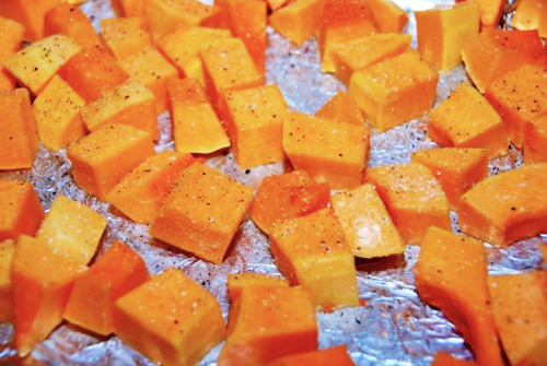 Cubed pieces of butternut squash seasoned with ghee, salt, and pepper.