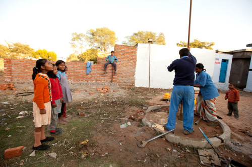 Trained local well mechanics repair a broken water well as kids from the community watch. Learn more about sustainable access to clean water in rural India at www.theadventureproject.org.