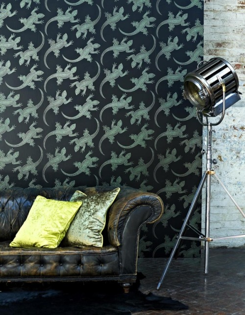 Gecko-printed wallpaper lends a playful reptilian touch to a worn leather Chesterfield sofa.