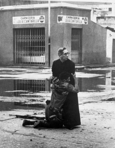 Priest Luis Padillo offers last rites to a loyalist soldier who is mortally wounded by a sniper during military rebellion against President Bétancourt at Puerto Cabello naval base.  Year: 1962 Photographer: Héctor Rondón Lovera Country: Puerto Cabello, Venezuela