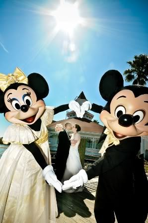 "How adorable is this Mickey and Minnie Wedding photo? I love how Mickey and Minnie are ""framing"" the happy Disney bride and groom!"