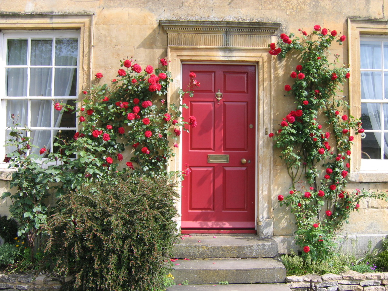enchantedengland:    Red door, climbing roses, Cotswold cottage- next to Rye this must be England at its most picturesque. This is in Moreton-on-Marsh, one of the lesser photographed Cotswold villages, in Gloucestershire. (UGArdener on flickr)  Cloggy:— We love Morton-in-Marsh. Stayed thereabouts several times. One time we were holidaying in Bournemouth and broke our journey at Morton-in-Marsh on the way down and it took us all our willpower to tear ourselves away and continue on.