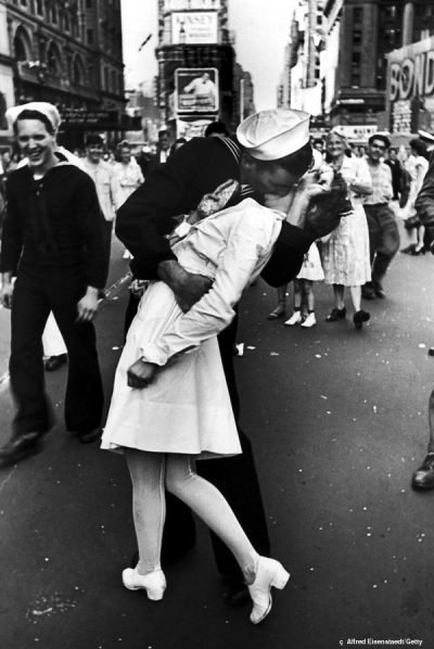 "Inspirational Photographer Essay                     Alfred Eisenstaedt was a German-American photographer and photojournalist born into a Jewish family of Dirschau, West Prussia, Imperial Germany in 1898 and died in 1995 at the age of 96. Alfred Eisenstaedt's candid photographs command the attention of the audience by showing captivating scenes such as this of the Celebration of V-J Day on August 14th, 1945 in Times Square, New York City. His dramatic approach to real life events creates pathos for the viewers and allow for successful photographs. Alfred also had a special technique behind his photos. He admitted, ""They never saw me clicking away. For the kind of photography I do, one has to be very unobtrusive and to blend in with the crowd."" For the photo of the V-J Day Celebration, Alfred explained ""[he] saw a sailor running along the street, grabbing any and every girl in sight…I was running ahead of him with my Leica looking back over my shoulder… I turned and clicked the moment the sailor kissed the nurse."" In all of his works, Alfred Eisenstaedt captures fearless historic moments, feeling as if ""its more important to click with the people then to click the shutter"". With this being said, I feel as if his goal of this V-J Day photograph was to capture a historic yet spontaneous moment following an announcement of the end of the war with Japan. His realistic approach to photography and subject of every day people allowed his photographs to be memorable since they were influenced by social, political and economic factors of his time period. By being one of the four original photographers of LIFE Magazine, producing over 2,500 assignments and 92 covers, Alfred was able to communicate his message through the media, enabling the world to experience history and current events through his photographs.            The image of the V-J Day Celebration is framed with the subjects in the middle of a crowded street in New York City known as Times Square. With an audience men and women watching, an American sailor kisses a young nurse, expressing his joy of the announced victory over Japan. The overall lighting style creates great contrast of light and dark, with the bright light of the background and an emphasized focal point of the couple. The main light source is coming from the sun, considering the photograph was taking outdoors, with brighter light in the background and to the right side of the photo. The photographer did not really manipulate the light to create a mood since this photograph was taken quickly in the spur of the moment, unplanned during a historical event. Thus, Alfred's vantage point was standing eye level with the subjects as they were running in the crowd. This photograph became a skilled and successful image that arose from pure timing and luck."
