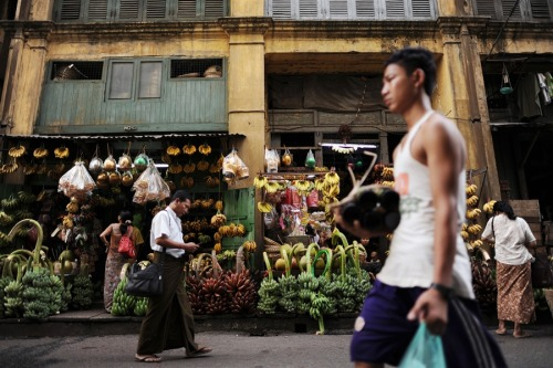 fotojournalismus:  Residents walk past shops selling bananas in Yangon on March 29. More than two decades after its stolen election win, Aung San Suu Kyi's opposition party is set for a dramatic political comeback in Myanmar polls which could herald an easing of sanctions. The upcoming vote is seen as an important vote of confidence for the country as it continues on the road to political and diplomatic reform.  [Credit : Christophe Archambault / AFP / Getty Images]