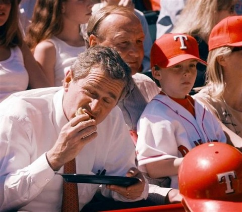 Like his father, the 43rd US President George W. Bush is posed digesting a ballpark hot dog during an opening-day game between the Texas Rangers and the Chicago White Sox in Arlington, Texas on March 31, 1998