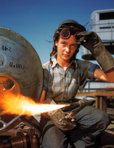 A welder at a boat-and-sub-building yard adjusts her goggles before resuming work, October, 1943. By 1945, women comprised well over a third of the civilian labor force (in 1940, it was closer to a quarter) and millions of those jobs were filled in factories: building bombers, manufacturing munitions, welding, drilling and riveting for the war effort. Pretty lady.