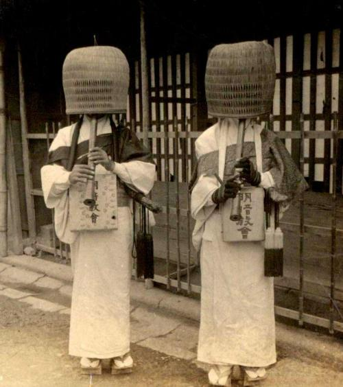 Komusō, Japanese mendicant monks, characterized by the straw baskets worn over their heads while playing Japanese flutes (known as shakuhachi) during the collection of alms. Photograph by Julian Cochrane (1904).