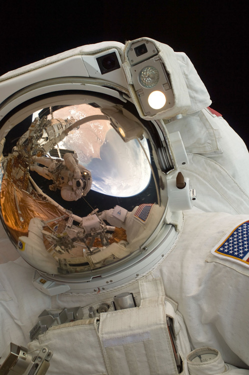 Spacewalking Astronaut John Grunsfeld. A close-up of Astronaut John Grunsfeld shows the reflection of Astronaut Andrew Feustel, perched on the robotic arm and taking the photo. The pair teamed together on three of the five spacewalks during Servicing Mission 4 in May 2009.