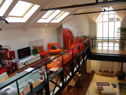I really like the massive window at the end and all the skylights. This loft looks perfectly cluttered and the colour scheme contrasts nicely with the potted plants! - H