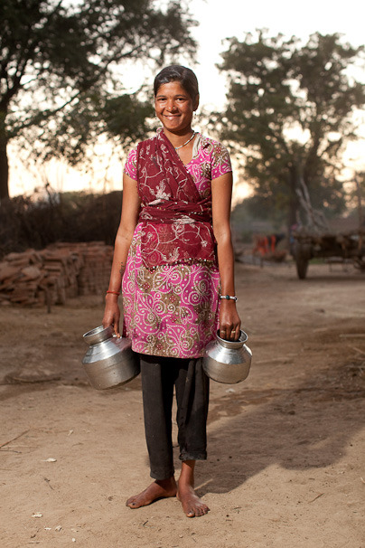 A young woman on her way to get clean water within her community.  By investing in sustainable solutions to the water crisis, you can help even more young women continue to have accessible clean water, providing the community with better health and increased productivity. Learn more about how you can make an impact: www.theadventureproject.org.