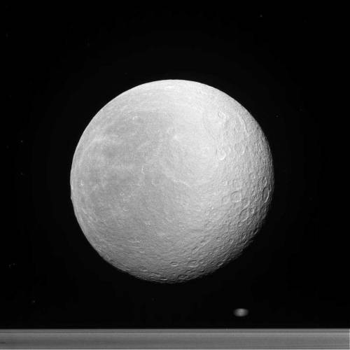 Postcards From Saturn Saturn's second-largest moon Rhea, in front of the rings and a blurred Epimetheus (or Janus) whizzing behind. Acquired March 29, 2012.