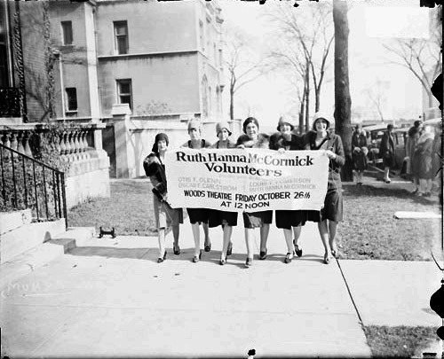 Six young women carrying a banner advertising a meeting of the Ruth Hanna McCormick Volunteers in Chicago, Illinois. The women are: Mrs. Elizabeth Drake, Helen Farnum, Mrs.Edwin Hersey, Glee Viles, and Jane Schuttler. Chicago Daily News photo, 1928. Ruth Hanna McCormick served in the US House of Representatives from 1929-1931.