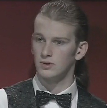 "Look who's back! Okay, maybe without that much hair. Peter Ebdon finds himself in the semifinals of the China Open after defeating Robbo in a battle of tortoise tacticians. The former World Champion has been a bit under the radar lately - the death of his father last year caused him to ""fall out of love with life"" - but he seems to be entering a new chapter. We wonder if it has anything to do with his recent switch to veganism, which he wrote about in detail on a blog in Feburary. He's always seemed like a guy ready to take on new things despite anyone else's opinion, be it rocking a ponytail in his youth (see above), singing, or gradually becoming one of the most torturously deliberate players on the planet. But throughout those years he evidently harboured a nasty addiction to Pepsi and chocolate (""I know that a lot of people will probably laugh at that but… Sometimes, I would literally have cold sweats and shakes, if I didn't have one or two bottles of Pepsi in a day…"") A friend recommended he see the documentary Forks Over Knives, about controlling disease by rejecting animal-based and processed foods, and it got him to keep digging for more information. Another documentary, Earthlings, got him to see the moral side of veganism, and the die was cast. So all the best to Ebbo…though we have to content ourselves that his new energy won't translate to more speed at the table. :-) (Thanks to Snookerbacker for the blog link. Photo screengrab from Snooker Compilation (5) on YouTube)"