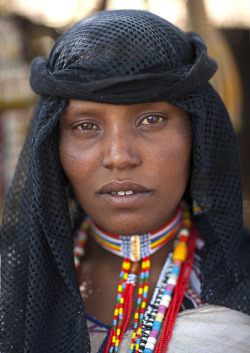Woman in Gada ceremony in Karrayyu tribe - Ethiopia by Eric Lafforgue on Flickr.Every eight years under a full moon, a tribe of Karrayyu priests gather in the Methara region, south of Addis Abeba, Ethiopia, for a ceremony to transfer power, this ceremony is named Gada. Five families share and govern the power. In two days, 10,000 people come, mainly by foot to help with the running of the ceremony. Absolutely no tourists are allowed in the proximity. After weeks of negotiation with the tribe's leader, I managed to obtain access to help at the ceremony. Throughout the entire negotiation process, it was never a matter of money, as is often the case with tribes, it was simply that the ceremony has never been open to foreigners. The chiefs finally accepted, the Karrayyus are living in particularly difficult times and their position is precarious. They want to make the world aware of their predicament ; the drought killing off their livestock and the government selling their fertile land to Saudi-Arabia, India and South Korea. Their former tribal wars with their neighbours, the Afars and the Sidamos, are beginning again. The number of young fighters wearing an ostrich feather in the hair acts of a badge of having killed another man, this acts as evidence of renewed conflict. The ceremony takes place in the desert with hundreds of temporary houses having been constructed specially for the Gadda. In front of each house there is cow fencing, the cow being a sacred animal, each one being named like one of their children. A mound of dry cow pat decorated with yellow fruit draws the boundary and the limit that nobody will dare to pass. Inside the house, each family has brought their bugée mataas, a strip of artistically, studded leather, their only valuable object. In front of the fences, the home owner waits for the ritual gifts that the visitors have come to offer them : milk, butter, sorghum … An accurate list of what has been offered is kept by a sort of official or clerk. As night falls, Karrayuus who have not managed to find the friends begin to shout their names, walking up and down in front of the houses. Some send texts from the mobiles, the only infringement of tradition. At midnight, the tribal danses begin, the mass circle forms, the warriors, the Qondallas with their afro hair style leap up and down to show their power. The desert is no longer just an immense dust cloud. At the same time, a group of other men look for the daughter of the future chief. She hides and they must find her, they are fortunate enough to have help, a full moon. Everybody else waits. All of a sudden at 3am, the women who were sleeping using their dresses as duvets leap to their feet and start singing : the chief's daughter has been found ! The presents are then bought into the houses and the monstrous feast begins. In the early hours of the morning, one hundred cows are sacrificed. Their throats cut by the Gille, a long traditional blade. The Karrayuus smear blood on the foreheads of the children as a sign of protection. Later on towards midday, all of the men of power including the chief shave the heads meanwhile the women pierce their ears with acacia thornes. Dozens of cows are again sacrificed, and once again the hot blood is smeared on the mens' freshly shaven heads, even babies have their heads smeared. At this point, women are allowed to leave the camp. Then comes the solemn, formal moment of the ceremony, the two families face one another. Each holding blades of wildgrass, irrechas and symbols of power. In a mad scramble, the exchange takes place in just a few seconds. The new chief declares power and disappears immediately ! The former chief leaves with tears in his eyes, the warriors pump themselves up in every sense. Drunk with happiness, the chants and songs start again. Everyone agrees to repeat the ceremony, in just 8 years time.