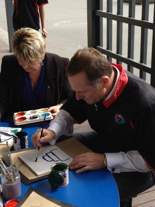 John Key looks at painting.