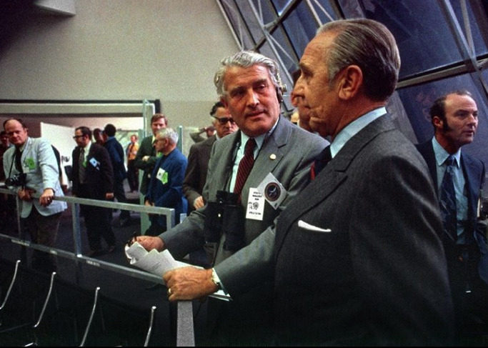 Von Braun talking with Dr. Kurt Debus in the Complex 39 firing room on morning of Apollo 14 launch - January 31, 1971. Also note that artist Robert McCall can be seen in the light colored coat off to the left.