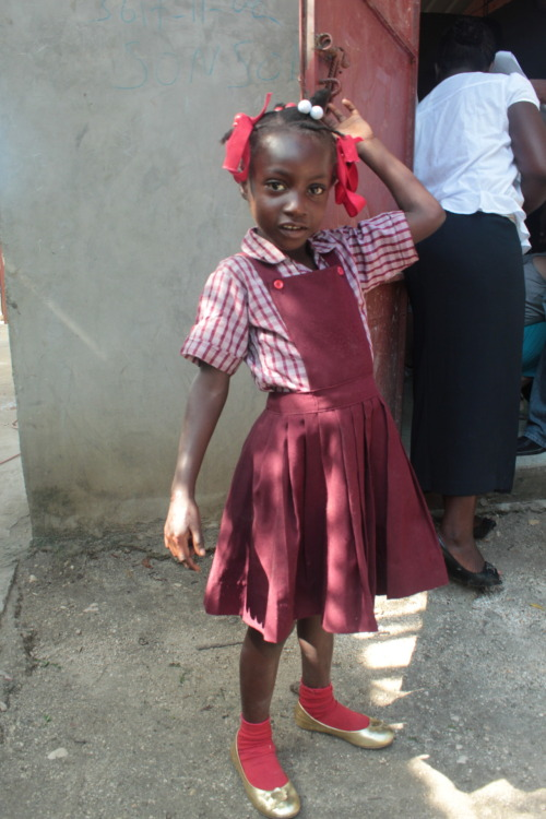 """Pic of the Day"" #18 This little girl is showing off her new gold shoes! We got to go to a school and fit the children for new shoes! Thanks to Haitians Helping Haitians for letting us be a part of this awesome experience! God's provision allowed us to give each student a new pair of shoes!"