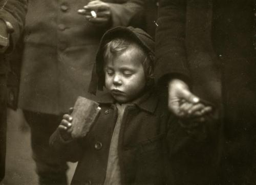 The Great War / First World War. A hungry child gets a piece of bread from a soldier. Weert, Holland / Netherlands, 1918.