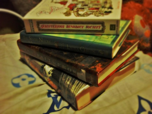 "Books I (Janelle) recently bought. :D The mysterious Benedict Society by Trenton Lee Stewart Plot: - ""ARE YOU A GIFTED CHILD LOOKING FOR SPECIAL OPPORTUNITIES?"" Dozens of children respond to this peculiar ad in the newspaper and are then put through a series of mind-bending tests, which readers take along with them. Only four children-two boys and two girls-succeed. Their challenge: to go on a secret mission that only the most intelligent and inventive children could complete. To accomplish it they will have to go undercover at the Learning Institute for the Very Enlightened, where the only rule is that there are no rules. But what they'll find in the hidden underground tunnels of the school is more than your average school supplies. So, if you're gifted, creative, or happen to know Morse Code, they could probably use your help.  The Silver Needle Murder by Laura Childs Plot:  - The Charleston Film Festival has brought Theodosia Browning and the staff of the Indigo Tea Shop a busy week of catering jobs. First up is the opening night gala at the historic Belvedere Theatre. Tinseltown and local luminaries seem to be mingling happily in the glamorously renovated lobby, but Theo notices that the atmosphere backstage is tense. Then famous director Jordan Cole is shot on his way to the podium, and the entire audience witnesses his death silhouetted across the scrim. Never has a festival started off with this big a bang. Fall of Frost by Brian Hall Plot: - In his most recent novel, I Should Be Extremely Happy in Your Company, Brian Hall won acclaim for the way he used the intimate, revelatory voice of fiction to capture the half- hidden personal stories of the Lewis and Clark expedition. In his new novel Hall turns to the life of Robert Frost, arguably America's most well-known poet. Frost, as both man and artist, was toughened by a hard life. His own father died when Frost was eleven; his only sibling, a sister, had to be institutionalized; of his five children, one died before the age of four, one committed suicide, one went insane, and one died in childbirth.  Told in short chapters, each of which presents an emblematic incident with intensity and immediacy, Hall's novel deftly weaves together the earlier parts of Frost's life with his final year, 1962, when, at age eighty- eight, and under the looming threat of the Cuban Missile Crisis, he made a visit to Russia and met with Khrushchev. As Hall shows, Frost determined early on that he would not succumb to the tragedies life threw at him. The deaths of his children were forms of his own death from which he resurrected himself through poetry—for him, the preeminent symbol of man's form-giving power. A searing, exquisitely constructed portrait of one man's rages, guilt, paranoia, and sheer, defiant persistence, as well as an exploration of why good people suffer unjustly and how art is born from that unanswerable question, Fall of Frost is a magnificent work that further confirms Hall's status as one of the most talented novelists at work today. Memorial by Bruce Wagner Plot: - Joan Herlihy is a semi-successful architect grasping at the illustrious commission that will catapult her to international renown, glossy de cor magazines, and the luxe condo designs of Meier, Koolhaas, and Hadid: the incestuous cult of contemporary Starchitects. Unexpectedly, she finds her Venice Beach firm on the short list for a coveted private memorial — a Napa billionaire's vanity tribute to relatives killed in the Christmas tsunami — with life-changing consequences. Her brother Chester clings to a failing career as a location scout before suffering an accidental injury resulting from an outrageous prank; the tragicomic repercussions lead him through a maze of addiction, delusion, paranoia — and ultimately, transcendence. Virtually abandoned by her family, the indomitable Marjorie Herlihy — mother, widow, and dreamer — falls prey to a confidence scheme dizzying in its sadism and complexity. And unbeknownst to Marj and her children, the father who disappeared decades ago is alive and well nearby, recently in the local news for reasons that will prove to be both his redemption and his undoing. Spiraling toward catastrophe, separate lives collide as family members make a valiant attempt to reunite and create an enduring legacy. To rewrite a ruined American dream."