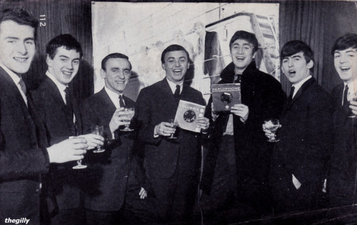 Brian Epstein's two top groups - minus Ringo - meet up for a celebration drink.  LtR: Les Maguire, Les Chadwick, Freddy Marsden, Gerry Marsden, John Lennon, George Harrison, Paul McCartney.  Photo by Peter Kaye. The picture behind them is of the Beatles on board the Salvor taken in September 1962