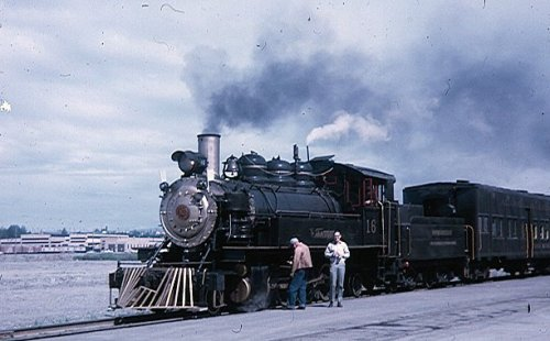"Baldwin 2-8-2 - ""Moose Gooser"" Alaska Railroad #16 - Anchorage, AK. June 1967. The locomotive was acquired by the West Coast Railway Association in 1964. In 1967 No. 16 was leased to the Alaska Railroad who were in need of a steam locomotive with which to celebrate Alaska's centennial. The Alaska Railroad ignominiously named their acquisition the ""Moose Gooser"". Returned from Alaska Railroad, it was sent to Vancouver Island in 1970 No.16 was built by Baldwin Locomotive Works for C. R. McCormick , a large Washington state logging company the year the Great Depression began. Typical of thousands of powerful ""Rod"" engines, No. 16 was the standard Baldwin logging locomotive design. With a 2-8-2 wheel arrangement this ""Mikado"" type locomotive has relatively small drivers, only 45"" in diameter giving power rather than speed. The centre 2 drivers are ""blind"" which means they do not have flanges. This enables No. 16 to negotiate the very sharp curves which were found on logging railways. No. 16 was built as a Saddle Tank engine. The water tanks were carried over the boiler like a saddle. Credit: Paul O'Garra"