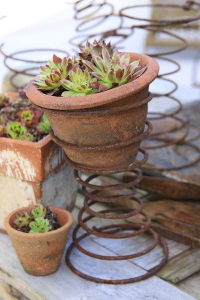 mamisgarden:  unconsumption:  6 ideas for repurposing springs Into a rustic or industrial look? Consider using springs, from lighter-weight bed springs to more sturdy automotive types, in creative ways like these: Individual springs enhancing a garden or tabletop. (image above, via Sjarmerende Gjenbruk)  Another tabletop idea. (via the same blog, here)  Set of springs repurposed as vertical storage. (image from Better Homes and Gardens; spotted on Pinterest here)  Springs made into lighting. (featured previously on Unconsumption here)  Truck springs fabricated into stools. (via House Beautiful)  Industrial springs made into sculptural light forms in a garden. (via Paradis Express blog)  the stools!   Oh! I want to do the thing with the pots.