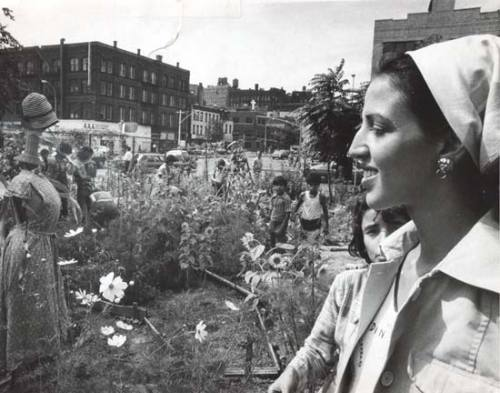 "Liz Christy in 1975, in one of the Lower East Side gardens she started. Photo by Donald Loggins.  ""The collective work of homesteaders and squatters to stabilize an environment of spiraling decline was joined by the Lower East Side's community garden movement, which sought to reclaim turf from encroaching urban blight. The resident gardeners set out to transform vacant lots strewn with trash, bricks, old appliances, and automobiles into green spaces. The movement's first community garden began in 1973, when a group of residents threw balloons containing plant seeds and bulbs into a large fenced-in parcel on Houston Street near Bowery. The activists, who called themselves Green Guerillas, assisted local residents and block associations in starting gardens and, at times, gaining permission to use city-owned properties…"" - Christopher Mele, Selling the Lower East Side: Culture, Real Estate, and Resistance in New York City."
