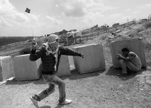 politics-war:  A Palestinian protester uses a sling to throw a rock at Israeli security forces.