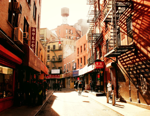 "Doyers Street. Chinatown, New York City.  Out of the way streets tell a wealth of tales. The bright afternoon sun beats down on old decaying walls and fire escapes creating elongated shadows that seem to stretch indefinitely. If the well-worn awnings could talk, just think of the secrets they would reveal.  This particular photo is of Doyers Street, one of my favorite out of the way streets. It is a winding street that curves around and is tucked away from its hectic surroundings. The street is only about 200 feet long and runs from Pell Street to Chatham Square. It's home to very old tenements and long-standing businesses like The Nom Wah Tea Parlor which opened in 1927.   In the early 20th century the curve in the street was known as ""the Bloody Angle"" because of a plethora of violent acts carried out by Chinatown gangs. The expression 'hatchet man' is said to have come from this era and these violent acts which often included hatchets. While the street is not bloody or violent today, it's worth a visit to soak in the history, vibe and incredible scenery.  —-  I wanted to thank those who helped me out this past weekend with the Artists Wanted contest. The response warmed my heart. I used to be phobic and against contests for various reasons but I am realizing that I need to put my photography out there in different ways and I can't let failure or fear of failure prevent me from doing that.  For those who didn't see my post, you can still help me out by going to my contest entry page and clicking COLLECT ME  Thanks, once again. I have so many dreams that I hope can take flight with my photography and it really makes me emotional when I think of the supportive friends I have made along the way in various online communities who inspire me in so many ways.  —-  View this photo larger and on black on my Google Plus page   —-  Buy ""Wealth of Tales - Doyers Street - Chinatown - New York City"" Posters and Prints here, email me, or ask for help."