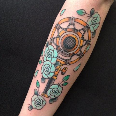 This was done by Vinny Romanelli at Red Rocket Tattoo in NYC. He's multi-talented and really well known for his portraits. This is a carbon-ring microphone (steampunk style). I'm a singer in a band and an activist so the microphone just seemed to fit me. You can see his work at www.tattoosbyvinny.com.