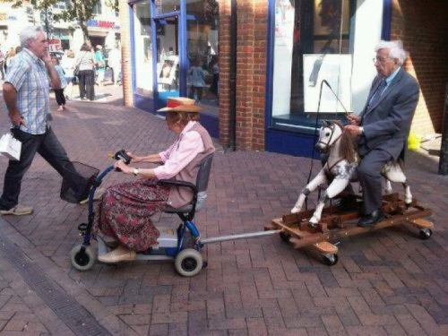 Old Woman on Scooter Pulls Old Man on Toy Horse   Run, Shadowfax! Show us the meaning of haste!