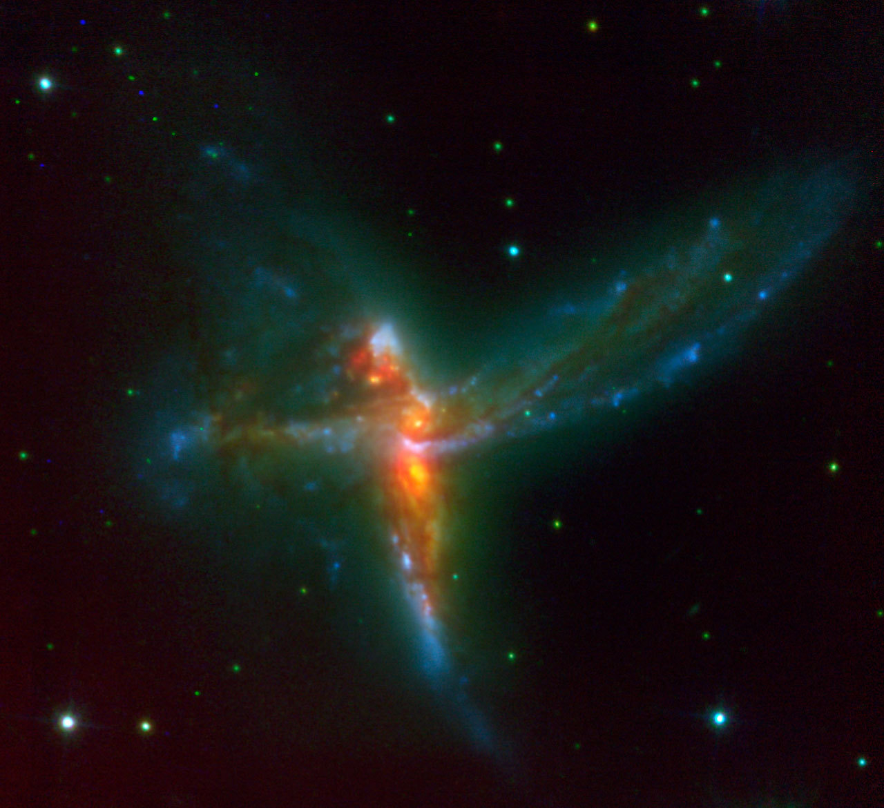 spacettf:  ESO - eso0755a The Tinker Bell Triplet Using ESO's Very Large Telescope, an international team of astronomers has discovered a stunning rare case of a triple merger of galaxies. This system, which astronomers have dubbed 'The Bird' - although it also bears resemblance with a cosmic Tinker Bell - is composed of two massive spiral galaxies and a third irregular galaxy. In this image, a 30-min VLT/NACO K-band exposure has been combined with archive HST/ACS B and I-band images to produce a three-colour image of the 'Bird' interacting galaxy system. The NACO image has allowed astronomers to not only see the two previously known galaxies, but to identify a third, clearly separate component, an irregular, yet fairly massive galaxy that seems to form stars at a frantic rate. Credit: ESO