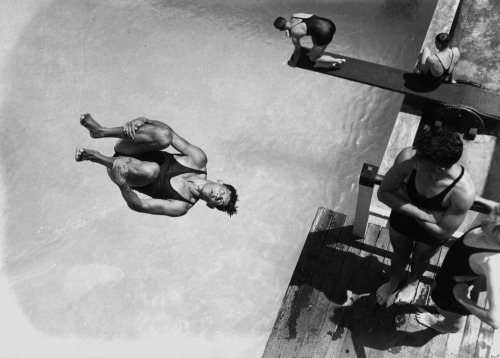 Diving at the Valley Baths, Brisbane, Queensland, 1938  Photographer: Unidentified Location: Fortitude Valley, Brisbane, Queensland, Australia; -27.454132, 153.036729 Description: An action shot of a young man diving from a tower at the Valley swimming pool. Other young men in swimming costumes are waiting in turn on the tower and on a lower diving board. The Baths are in Wickham Street, Fortitude Valley.