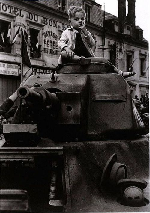A child sitting atop a tank during Charles de Gaulle's speech after the liberation of Paris by Allied forces, August 25, 1944. Photo by Robert Capa.