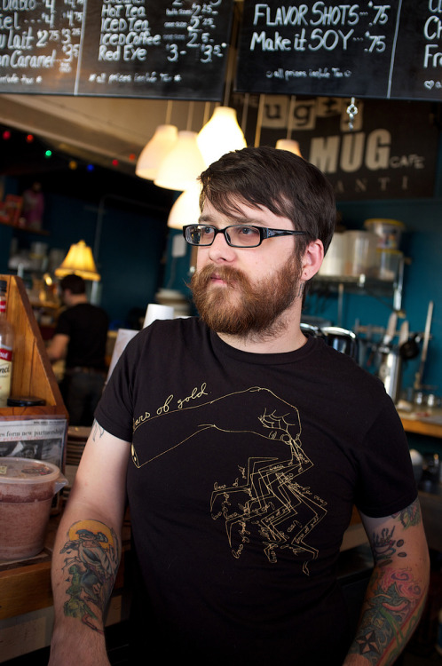 "Title: Eric ""Batman"" Mullins.I'm fond of 2 things… beardos and baristas! Put them together and you get a whole lot of awesome sauce, case in point - this photo of my friend Eric Mullins. He not only makes a mean coffee but he is a superhero!Side note: this shot is also Straight Out Of Camera (SOOC) with my Fujifilm X100 set to Provia/STANDARD using a custom white balance. I've been not only on a roll with these SOOC shots - but I strive for them. The X100 is totally my BFF and trusty sidekick!the UGLY MUG cafe and roasteryYpsilanti, Michiganwww.uglymugypsi.com"
