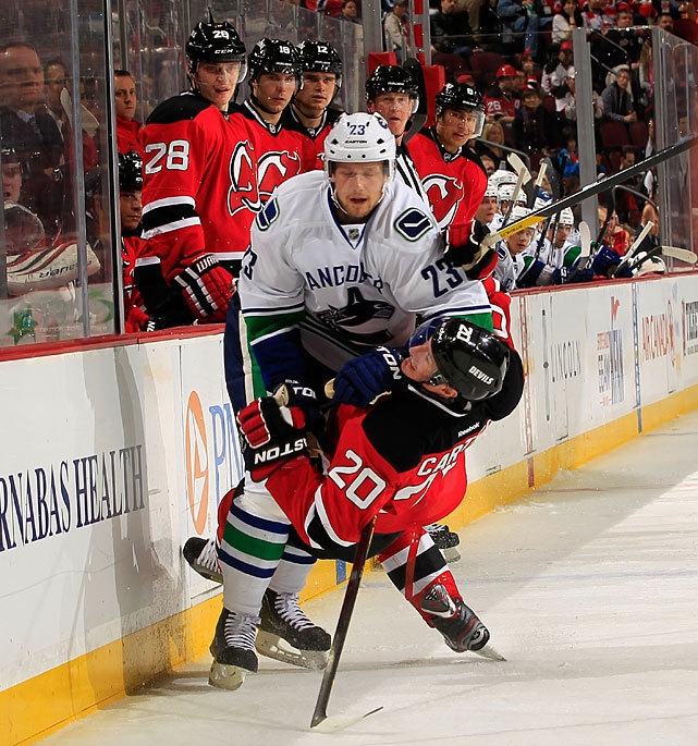 Vancouver's Alexander Edler flattens New Jersey's Ryan Carter during a Vancouver-New Jersey game in late February. The Canucks are heating up at the right time, winning all four of their games last week and ascending to first place in Adrian Dater's weekly NHL Power Rankings. (Chris Trotman/Getty Images) DATER: Canucks take top spot in weekly Power RankingsDATER: Handing out awards for the 2011-12 NHL season