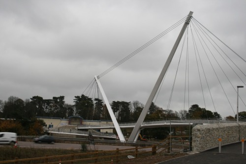 "The Eureka Skyway, Ashford, Kent  An Infection of Iconic Bridges. What are they for? To help transport people over an obstacle? Not if they were built in the last decade and a bit. Bridges are now a much beloved metaphor for councils and landowners, they ""connect communities"", ""cross boundaries"" and provide ""iconic"" structures for ""transforming the landscape"". But, why? Why do they have to do these things, why can't they just get people from one place to another? It's not hard to trace the lineage of this lust for iconicism. In the late 90s there was an abundance of money around to pay for anything transformative and shiny for the millennium. The two, vastly successful, examples of this trend that spring to mind are The Millennium Bridge in London (here) and The Millennium Bridge in Gateshead (here) but for these two landmarks there are dozens of others out there crossing lonely canals and motorways that have been built as icons but will never be such. I've always been slightly irked by the relentless lust for landmark status that has infected architecture in the last decade but it wasn't until I walked across the new Porth Teigr Outer Lock Crossing in Cardiff that I really contemplated its effect on bridges. The bridge in question, which you can see (here), doesn't even have a proper name because it crosses an incredibly short lock-entrance. The previous bridge was a small and inane affair but that simply will not do for an area so full of landmarks and breathless iconicism. So now we have the new bridge, a bright-red explosion of a bridge that clashes astonishingly with the low-key surroundings of the Norwegian Church and the Lightship. A £2.5m reminder of Cardiff Bay's incoherence and desperation. Why does something as simple as the crossing of a lock have to be turned into torturous architectural theatre? Why not just build a simple bridge for half the price? It seems almost unthinkable that a bridge could be built today that is simply a bridge, at least where there's money sloshing around to make it otherwise. There's a common process to be followed; architectural competition, council commission, local outrage/delight, sky-high costs, building delays, local paper grumbling and then finally the inaugural opening/spinning/lifting/swinging/blinking of the bridge. A great example of this process is in evidence (here) where we can see a half dozen 'iconic' designs for, what should be, a very simple crossing of a footpath over a motorway in Sheffield. There'd have been no local discontent if a low-key crossing was built here, it could have been done in about a month with a pre-fabricated steel walkway but, no, the council must have its icon so the locals have to wait longer for their bridge and when they get it it may well be a vortex or a porcupine.  Bridges aren't like buildings, there's no-one to look after them on a day-to-day basis. They rust and their metal dulls and people graffiti all over them. A bridge I cross often is Valentine's Bridge in Bristol which you can see (here), a curvy, suspended piece of nonsense that creaks incredibly loudly under foot and is always covered in stickers and gum and then there's the nameless footbridge not 200 yards downstream that is in an even worse state and is even uglier, see (here). I'm not arguing against all exciting bridges here, not at all, Stockton's Infinity Bridge is truly a landmark, see (here), but could Ashford really have dealt perfectly fine with a girder bridge instead of its £8m Eureka Skyway (here) and could Poole have not thought of something better to spend £37m on than a bascule bridge which was predictably beset by displays and chronically ugly warning lights, see (here). Please can someone tell me why a bridge can't just be a bridge any more and why something as simple and practical as this is so unfashionable and unthinkable to icon-obsessed councils and developers."