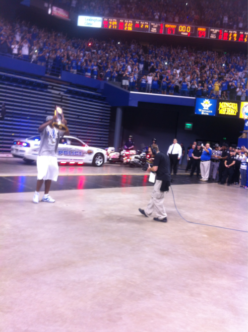 kentuckybasketball:  Darius Miller is the last player off of the bus and raises the Championship trophy in the air.