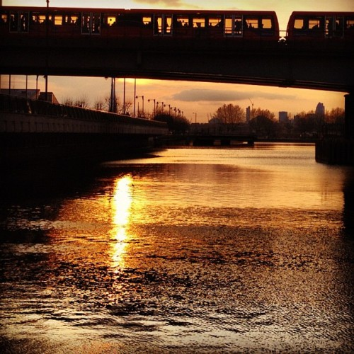 Through The Train & Under The Train #sunset #dlrtrain #dlr #trainviaduct #glass #water #dock #quay #reflection #skyline #ripples #heronquay #canarywharf #eastlondon #london #england #greatbritain #unitedkingdom #transport #lightrail #tfl #londontransport #whitecloud #greycloud #orange #glow #spring #evening #april #2012 #hefe #lux (Taken with Instagram at Canary Wharf Underground station)