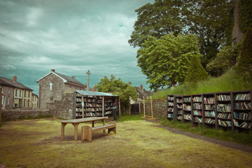 "The Honesty Bookshop, Hay-on-Wye by never meant to see on Flickr. The little town of Hay-on-Wye has over 40 bookshops and is known as the ""Second-hand Book Capital"" of the World. The picture shows the grounds of the open-air Honesty Bookshop, which is located in the grounds of the Hay-on-Wye Castle. Its books are available on open shelves 24 hours a day. When you've made your choice, you just put your money into the collecting box."