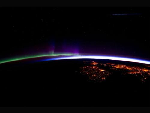 Our planet's horizon.  The night lights of the cities of Ireland, in the foreground, and the United Kingdom, in the back and to the right, are contrasted by the bright sunrise in the background. The greens and purples of the Aurora Borealis are seen along the rest of the horizon. This image was taken on March 28, 2012.